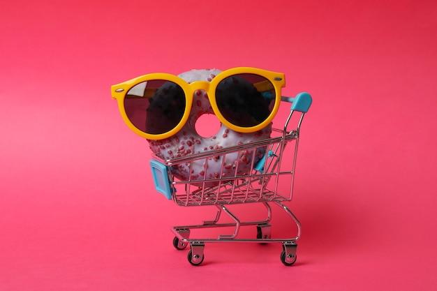 Sklepowy wózek z okularami przeciwsłonecznymi i pączkiem na różowym tle