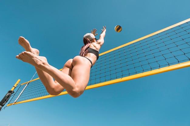 Skocz do sportu młoda kobieta gra w siatkówkę na plaży na tle błękitnego nieba. blokowanie piłki.