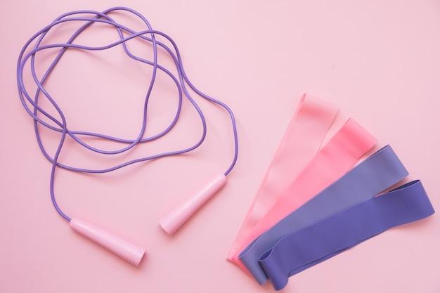 Skok lub skakanka i gumka fitness na różowym tle. trend fitness.