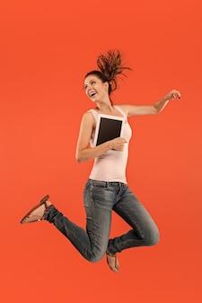 Skok młodej kobiety na niebieskim tle studio za pomocą gadżetu laptopa lub tabletu podczas skakania. uciekająca dziewczyna w ruchu lub ruchu.