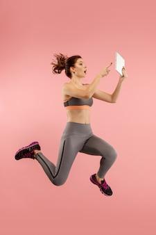 Skok młodej kobiety na niebieskim tle studio za pomocą gadżetu laptopa lub tabletu podczas skakania.