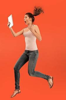 Skok młodej kobiety na niebieskim tle studio za pomocą gadżetu tabletu podczas skakania.