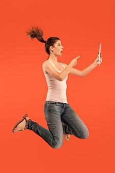Skok młodej kobiety na pomarańczową ścianę studio za pomocą tabletu
