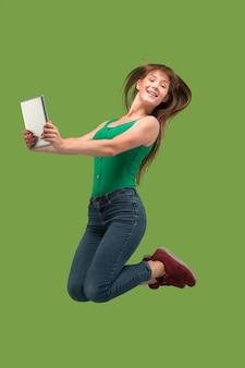 Skok młodej kobiety na zielono przy użyciu gadżetu laptopa lub tabletu podczas skakania. uciekająca dziewczyna w ruchu lub ruchu
