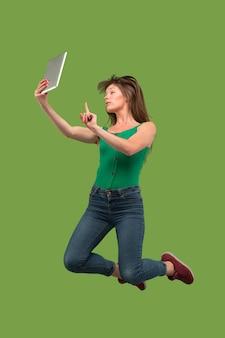 Skok młodej kobiety na zielonym tle studio za pomocą gadżetu laptopa lub tabletu podczas skakania. uciekająca dziewczyna w ruchu lub ruchu.