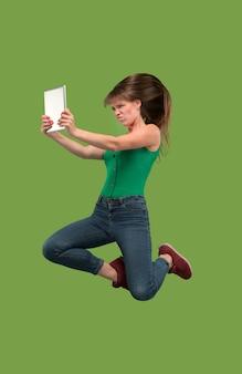 Skok młodej kobiety na zielonym tle studio za pomocą gadżetu laptopa lub tabletu podczas skakania.