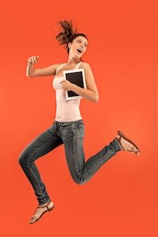 Skok młodej kobiety nad niebieskim studio przy użyciu gadżetu laptopa lub tabletu podczas skakania.