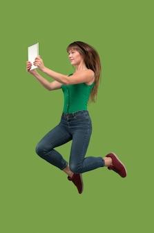 Skok młodej kobiety nad zielonym studio przy użyciu gadżetu laptopa lub tabletu podczas skakania.