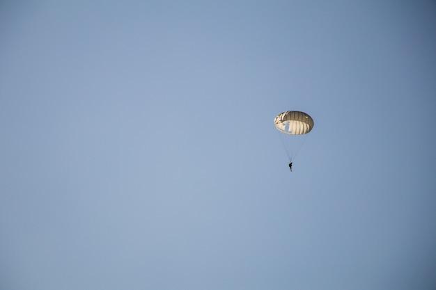 Skok spadochroniarza z białym spadochronem, wojskowy skoczek spadochronowy na niebie.
