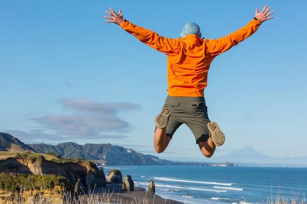 Skoki człowieka na wybrzeżu oceanu, nowa zelandia