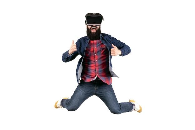 Skoki hipster w okularach wirtualnej rzeczywistości pokazując kciuk do góry, na białym tle na białej ścianie