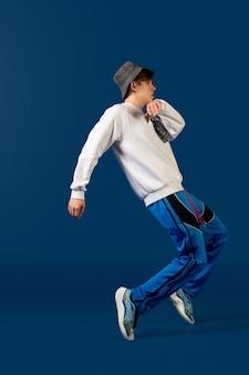Skoki. old-school fashioned młody człowiek taniec na białym tle na niebieskim studio