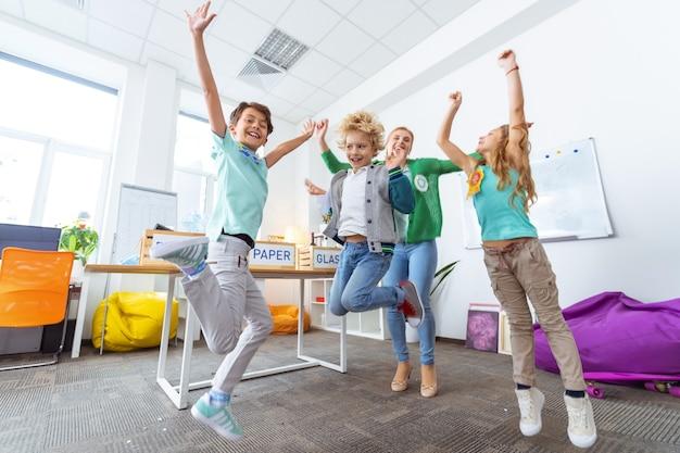 Skoki po sortowaniu. pracowite dzieci w wieku szkolnym i nauczycielka skaczą po udanym sortowaniu śmieci