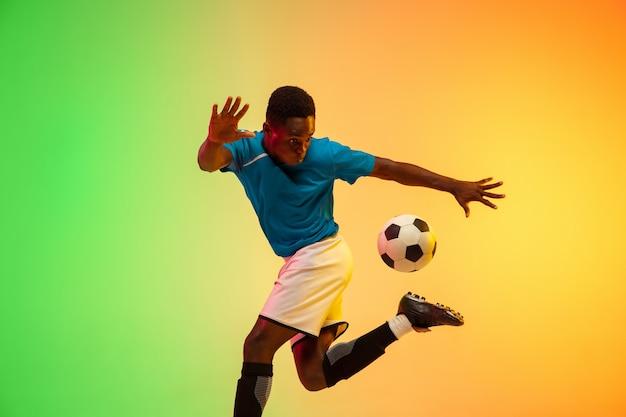 Skoki wzwyż. męska piłka nożna, trening piłkarza w akcji na białym tle na gradientowym tle studio w świetle neonowym. pojęcie ruchu, działania, osiągnięć, zdrowego stylu życia. kultura młodzieżowa.