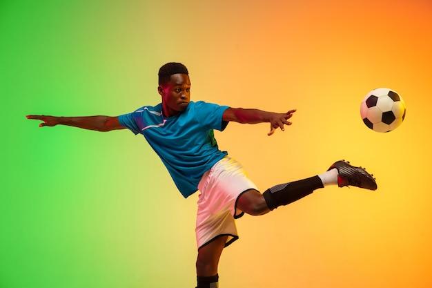 Skoki wzwyż męski piłkarz trenujący w akcji izolowany na gradientowym studio