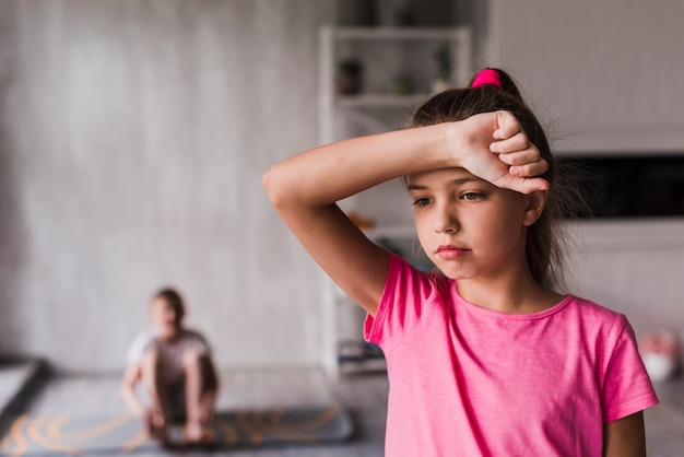 Skołowana dziewczyna z jej ręką na czoła pozyci przed zamazaną chłopiec przy tłem