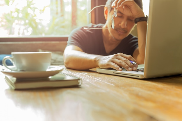 Skołowany mężczyzna pracuje na laptopie z oczami zamyka przeciw okno światłu.