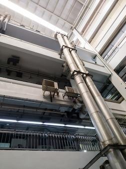 Skomplikowana metalowa rura systemu wentylacji wzdłuż tarasu na szczyt budynku w dużym szpitalu, powyżej widok z kopią.