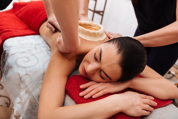 Skomplikowana procedura. przyjemna ładna dama ciesząca się uczuciem ciepłego oleju na plecach, podczas gdy mistrz utrzymuje go na miejscu
