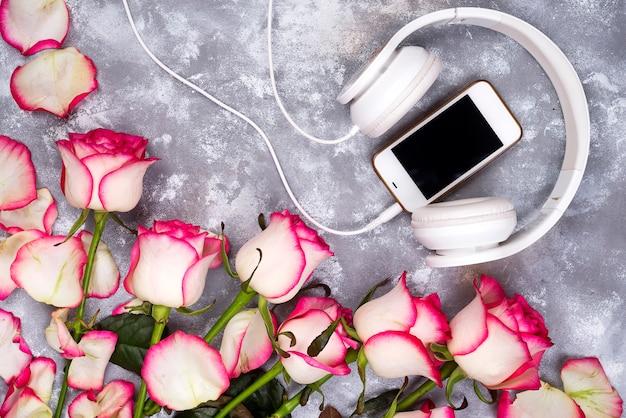 Skomponowana ramka róż i telefon komórkowy ze słuchawkami