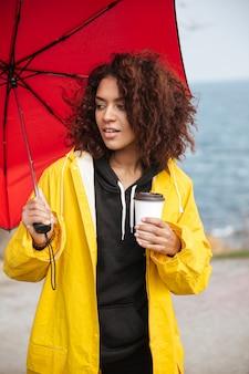 Skoncentrowana afrykańska kędzierzawa młoda dama chodzi outdoors i pije kawę.