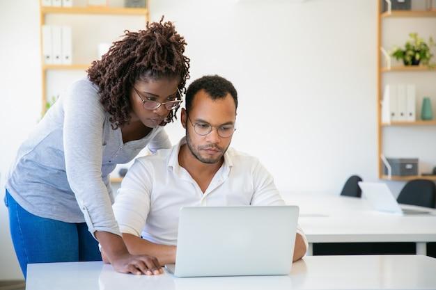 Skoncentrowana amerykanin afrykańskiego pochodzenia kobieta patrzeje laptop