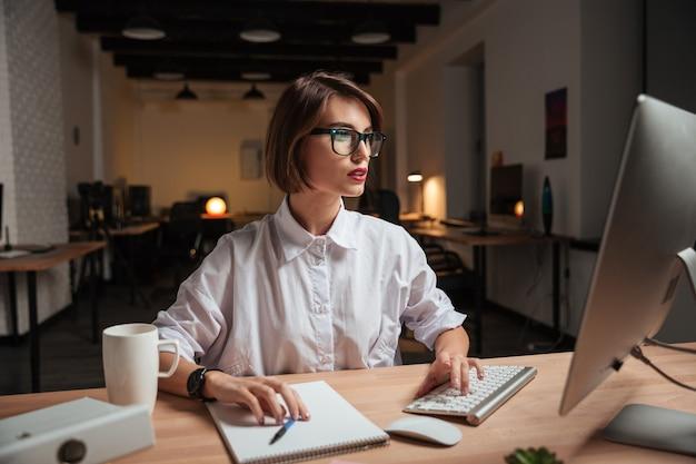 Skoncentrowana atrakcyjna młoda bizneswoman w okularach pracująca z komputerem w biurze