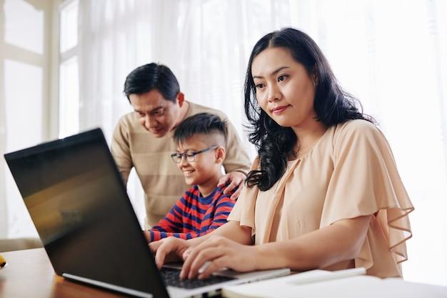 Skoncentrowana azjatka pracująca na laptopie, gdy jej mąż pomaga synowi w odrabianiu prac domowych