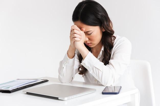 Skoncentrowana azjatykcia biznesowa kobieta jest ubranym biurowego ubraniowego obsiadanie przy stołem i modlenie trzyma ręki wpólnie