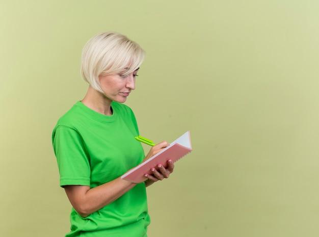 Skoncentrowana blondynka w średnim wieku kobieta stojąca w widoku profilu pisania na notesie za pomocą pióra na białym tle na oliwkowej ścianie