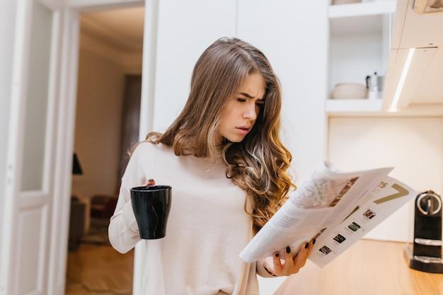 Skoncentrowana ciemnowłosa kobieta czyta magazyn rano