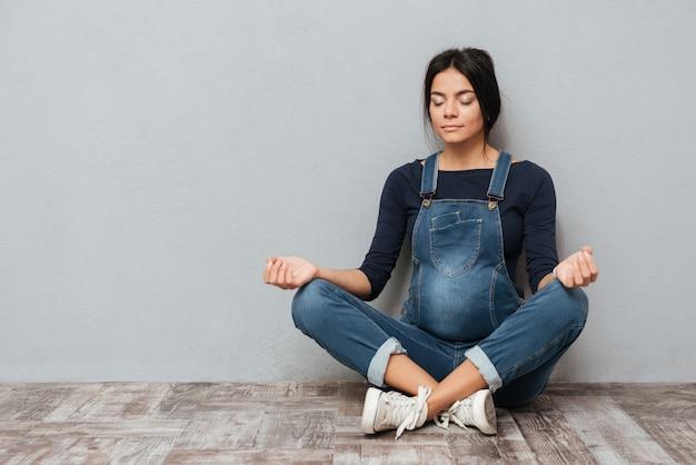 Skoncentrowana ciężarna dama siedzi na podłoga