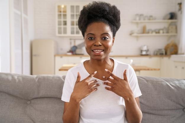 Skoncentrowana czarna dziewczyna rozmawiająca na seminarium internetowym, komunikująca się za pomocą aplikacji do wideokonferencji patrząc na kamerę internetową