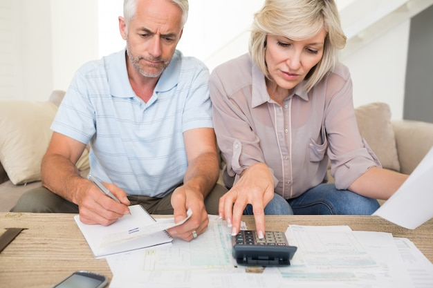 Skoncentrowana dojrzała para z rachunkami i kalkulator w domu