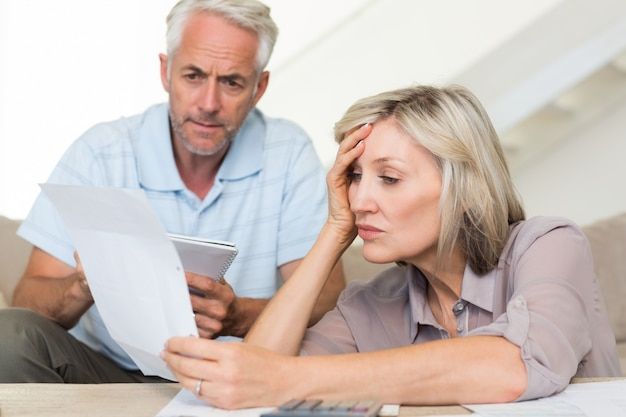 Skoncentrowana dojrzała para z rachunkami w domu