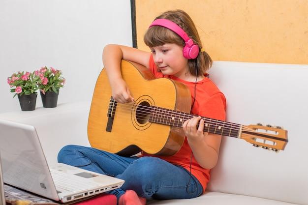 Skoncentrowana dziewczyna ćwiczy z gitarą akustyczną, siedzi na kanapie w domu