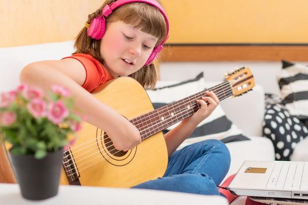 Skoncentrowana dziewczyna ćwiczy z gitarą akustyczną usiąść na kanapie w domu