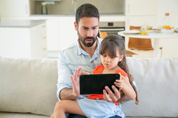 Skoncentrowana dziewczyna i jej tata korzystający z aplikacji online, oglądający film lub czytający razem na ekranie tabletu.