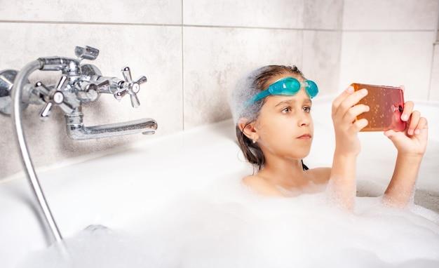 Skoncentrowana dziewczynka kaukaski w okularach pływackich robi selfie przy użyciu smartfona podczas kąpieli w wannie z pianką w domu