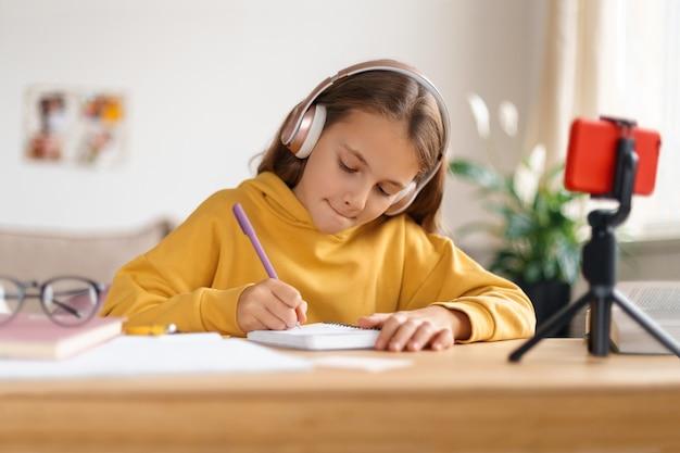 Skoncentrowana dziewczynka odrabia lekcje w swoim pokoju, ucząc się w domu, używając smartfona ze statywem i słuchawkami