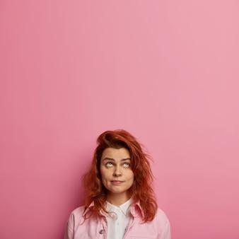 Skoncentrowana europejka o rudych włosach, zdrowej skórze, patrzy w górę, nosi różowe ubrania