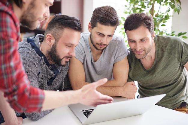 Skoncentrowana grupa mężczyzn siedzących przed laptopem