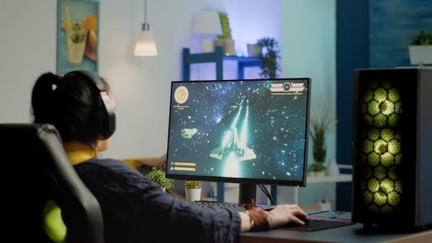 Skoncentrowana kobieta grająca w zestaw słuchawkowy zaczyna grać w kosmiczną strzelankę na wirtualnej rywalizacji na potężnym komputerze osobistym. esport cyber występujący podczas turnieju gier e-sportowych
