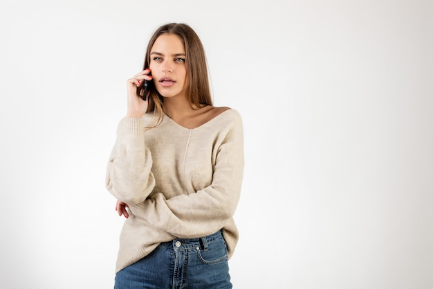 Skoncentrowana kobieta opowiada na telefonie odizolowywającym nad bielem