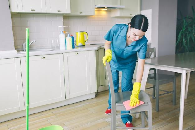 Skoncentrowana kobieta pochyla się w stronę krzesła i czyści je szmatą
