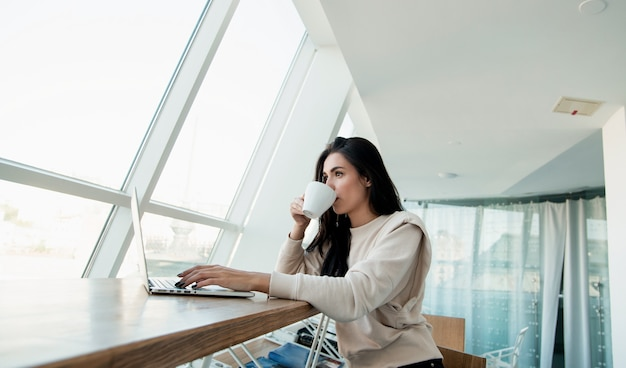 Skoncentrowana kobieta pracująca na swoim laptopie i pijąca kawę. koncepcja odzieży casual. freelancer brunetka kobieta pracuje w kawiarni i korzystających z napojów. pracownik samozatrudniony.