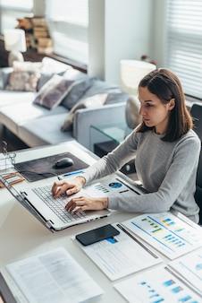 Skoncentrowana kobieta pracująca w domowym biurze na laptopie.