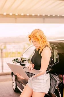 Skoncentrowana kobieta pracuje na laptopie obok samochodu