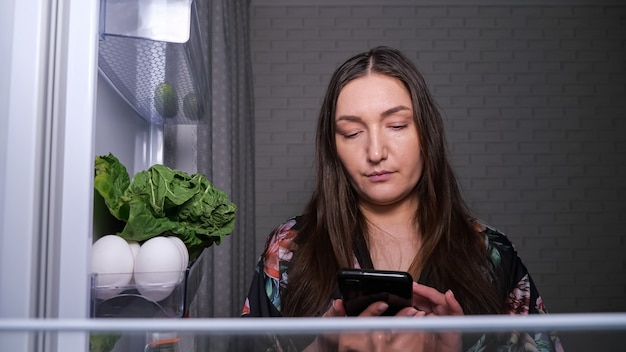 Skoncentrowana kobieta robi listę produktów spożywczych do kupienia