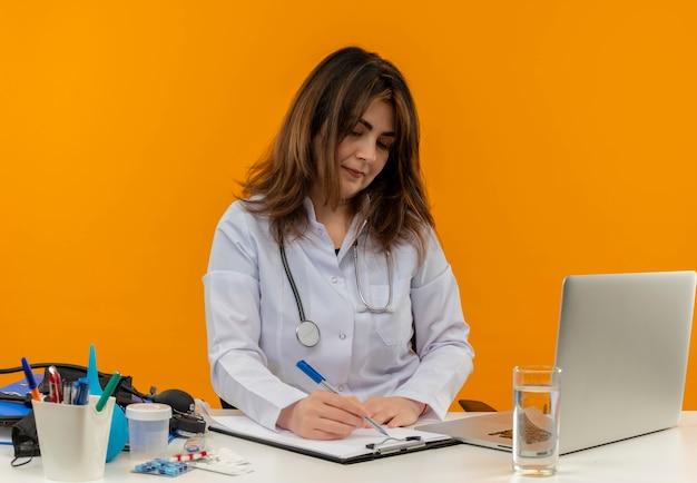 Skoncentrowana kobieta w średnim wieku ubrana w szlafrok medyczny i stetoskop siedząca przy biurku z narzędziami medycznymi laptop piszący piórem w schowku na białym tle